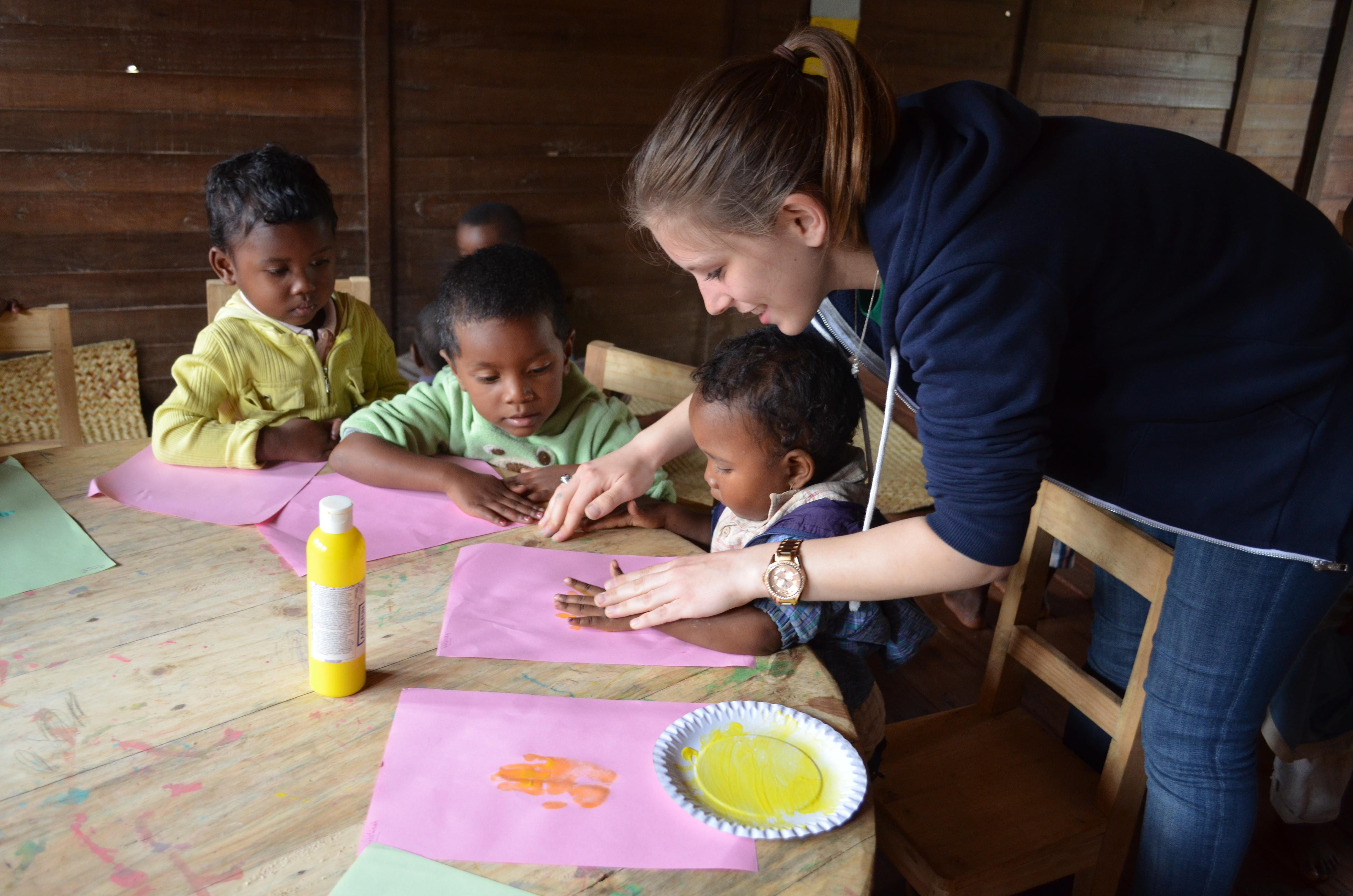 Projects Abroad volunteer working with children in Madagascar helps a group of children do hand printing at a day care centre.